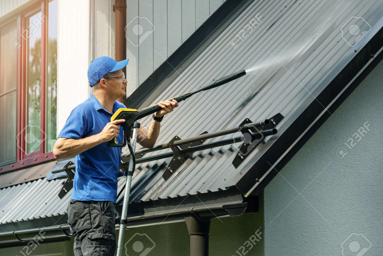 man standing on ladder and cleaning house metal roof with high pressure washer - 127197546