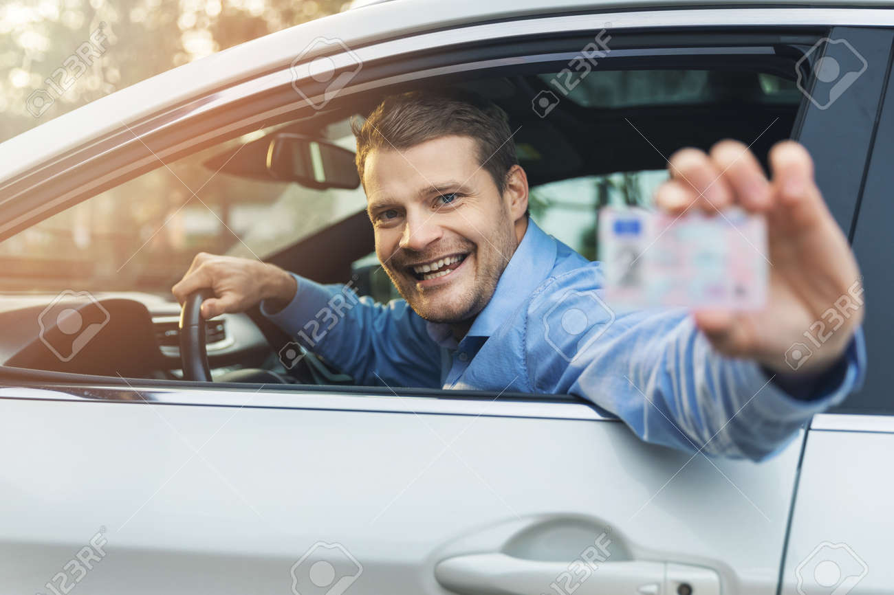 man sitting in the car and showing his driver license out of car window - 136326830