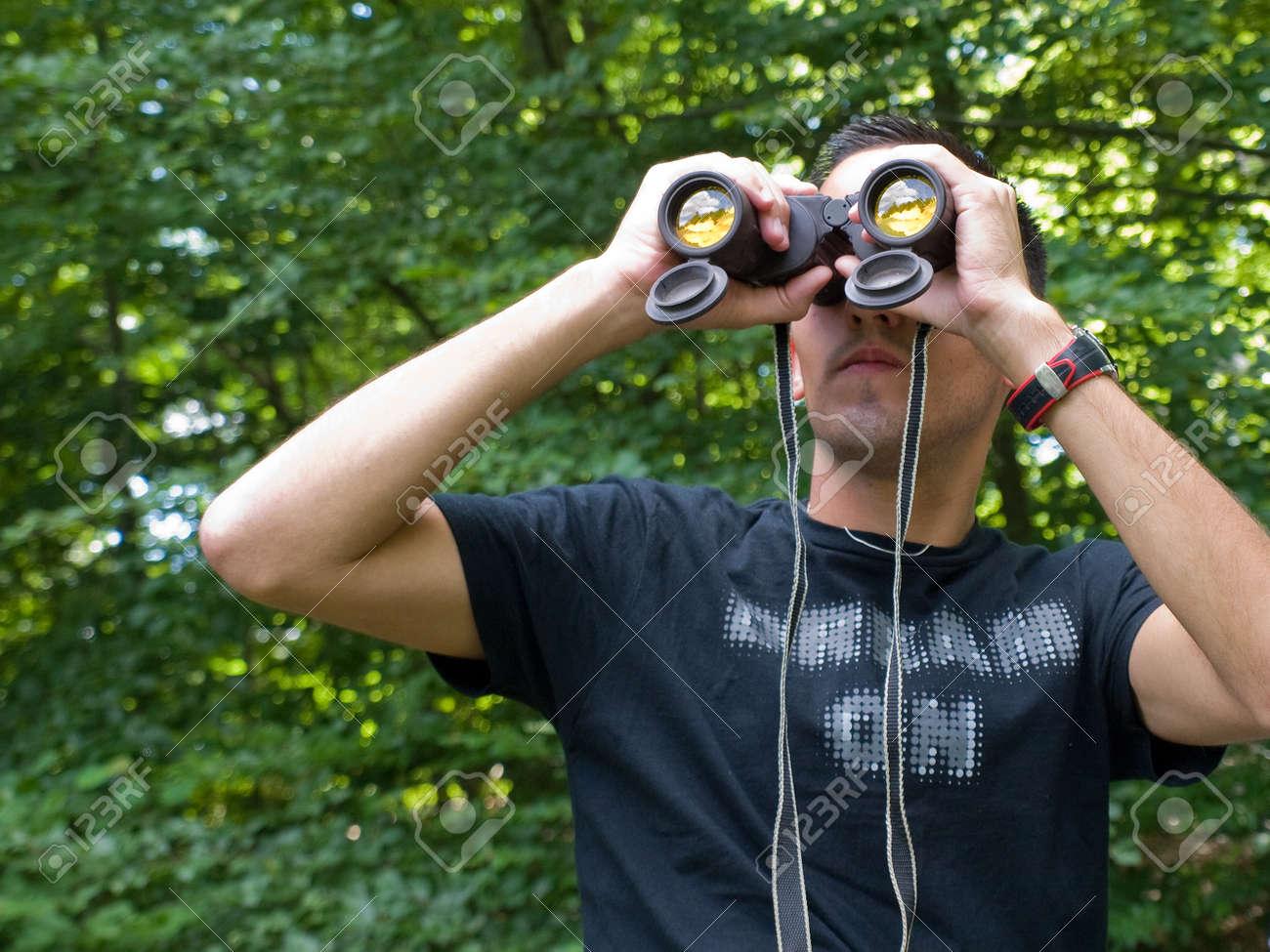 Junger mann sucht mit dem fernglas wandern während draußen in der