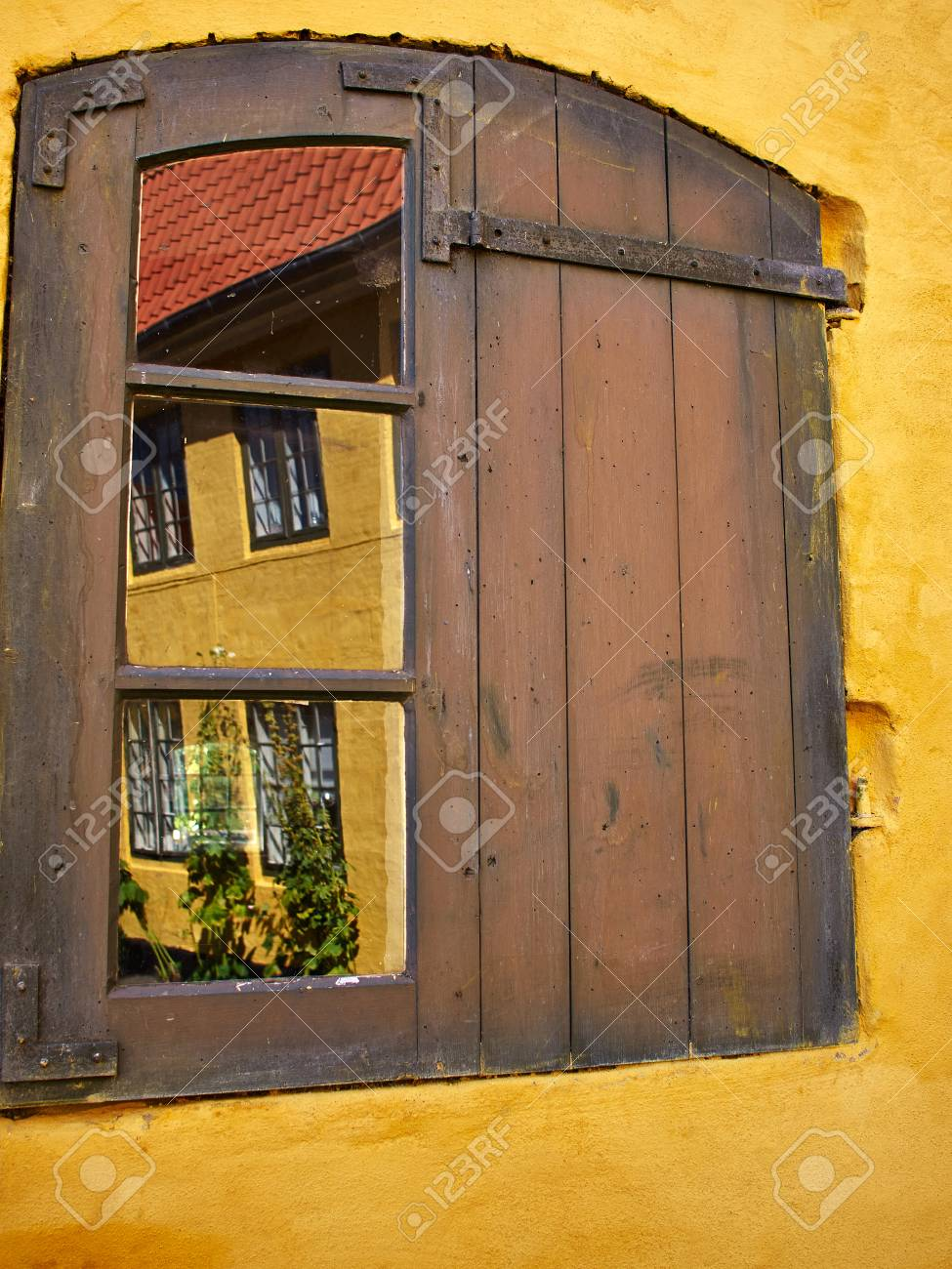 Rustic Window With Wooden Exterior Shutters On A Yellow Painted