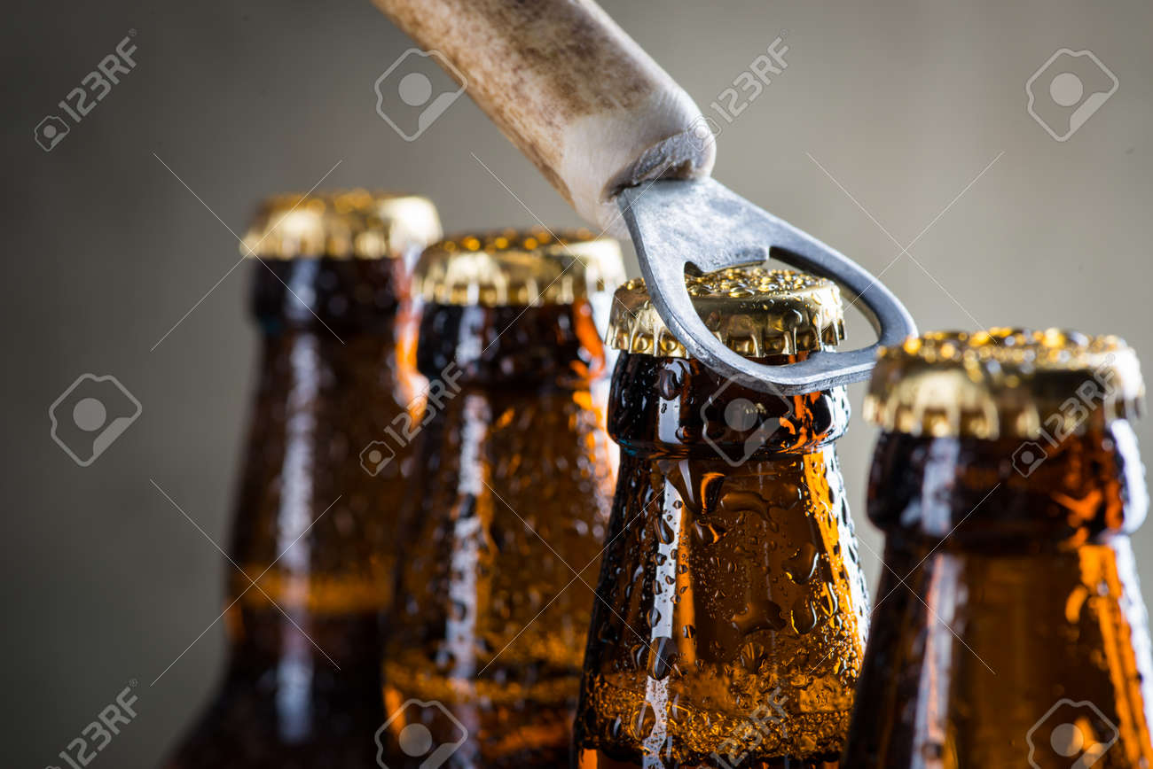 Brown ice cold beer bottles with water drops and old opener - 54104302