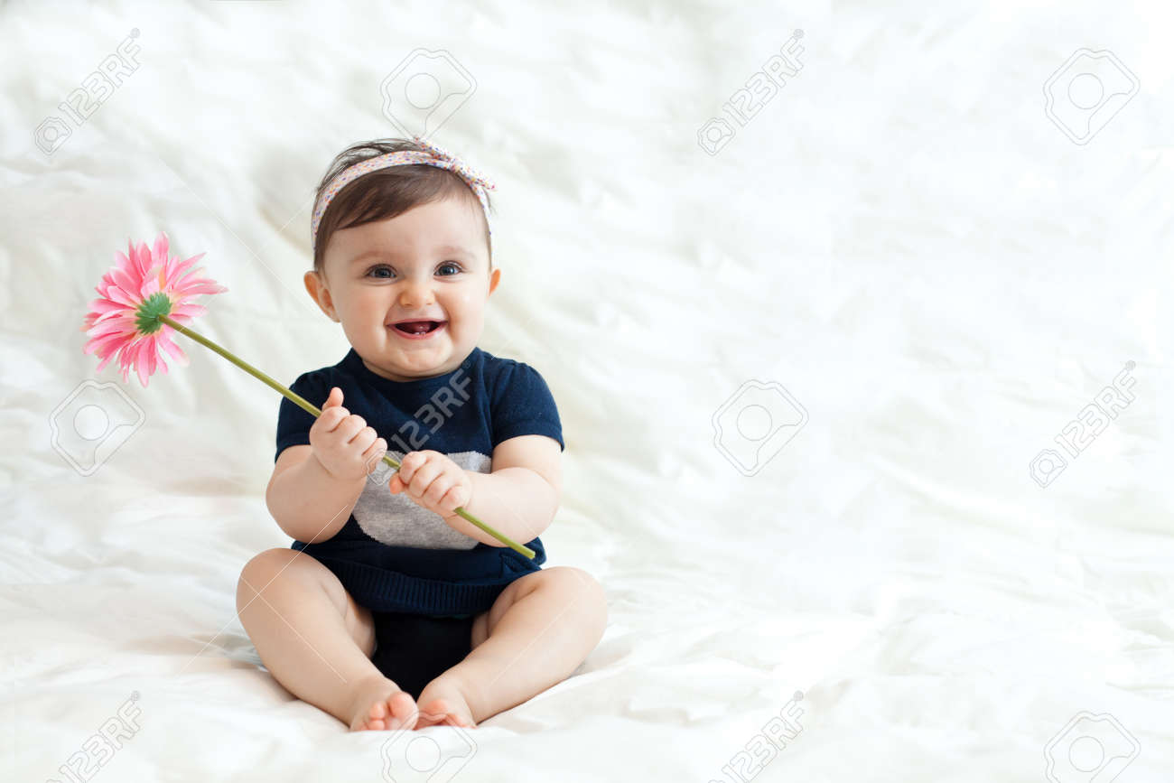 Portrait of cute baby girl 6 11 months playing with flower stock photo