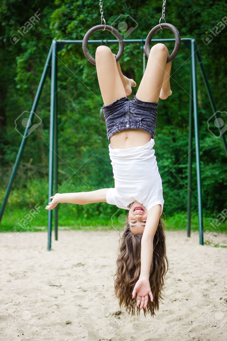 Girl Hanging Upside Down In A Playground Stock Photo, Picture And ...