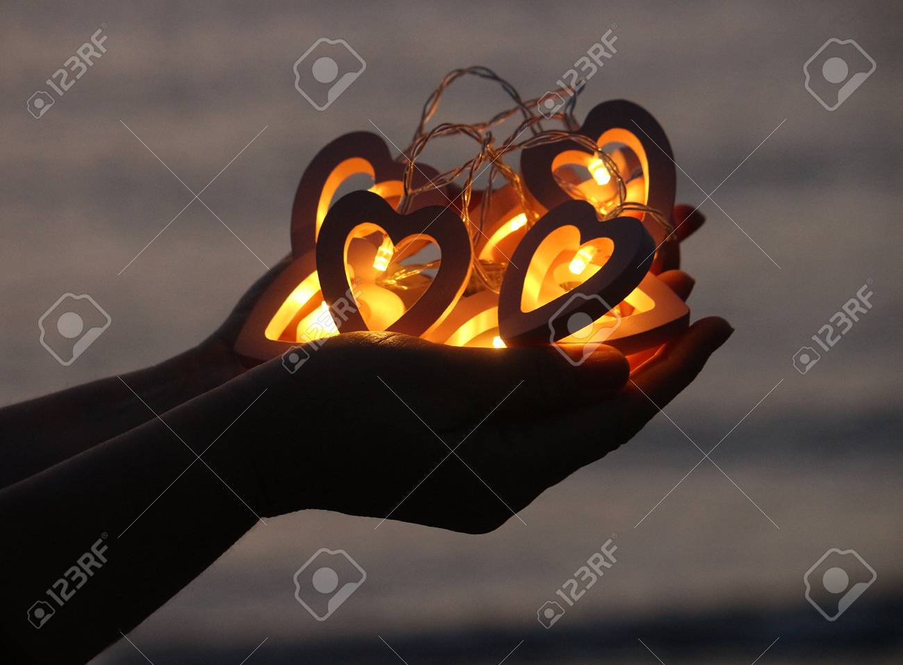separation shoes fbbb8 2dc83 Woman's hands holding heart shaped string lights