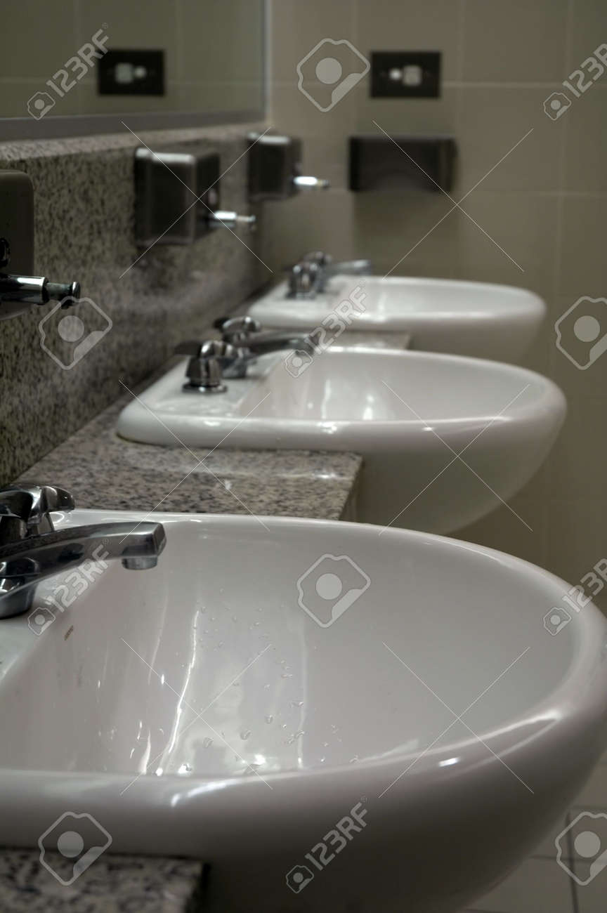 Three White Sinks In Public Toilets, Mirror On The Wall Stock Photo ...