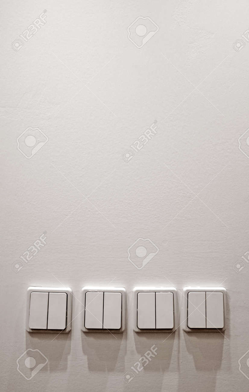 white wall with four plastic light switches, Stock Photo - 4513060