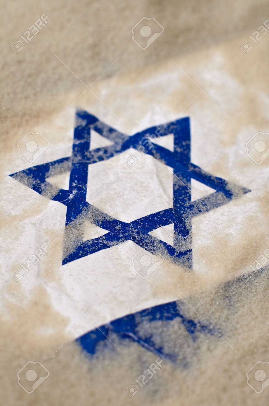 detail photo of an insreal flag burried in sand, david star in focus Stock Photo - 8095258