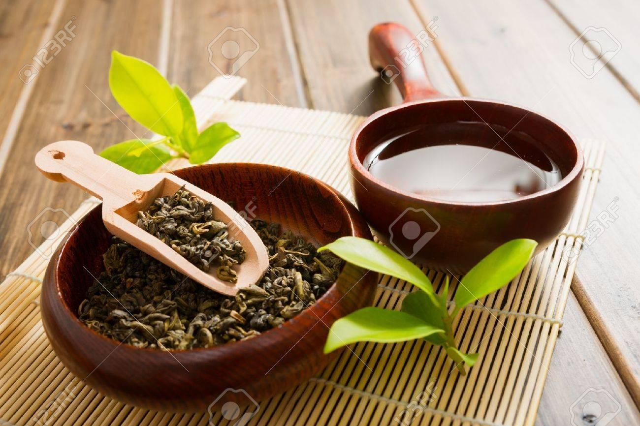 tea and tea leaves on bamboo mat on wooden table Standard-Bild - 16267825