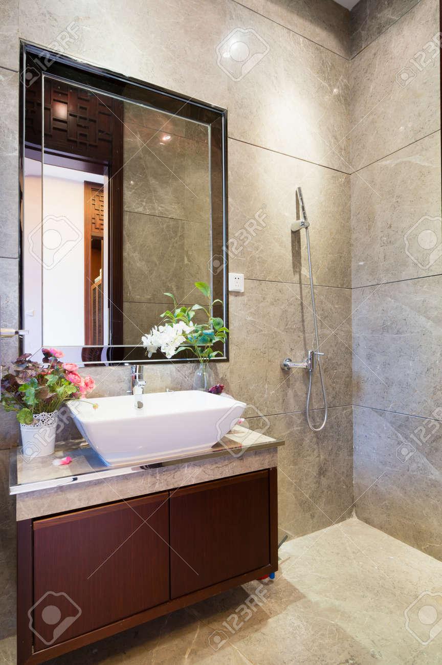 Moderno cuarto de baño con espejo, lavabo, armario y ducha