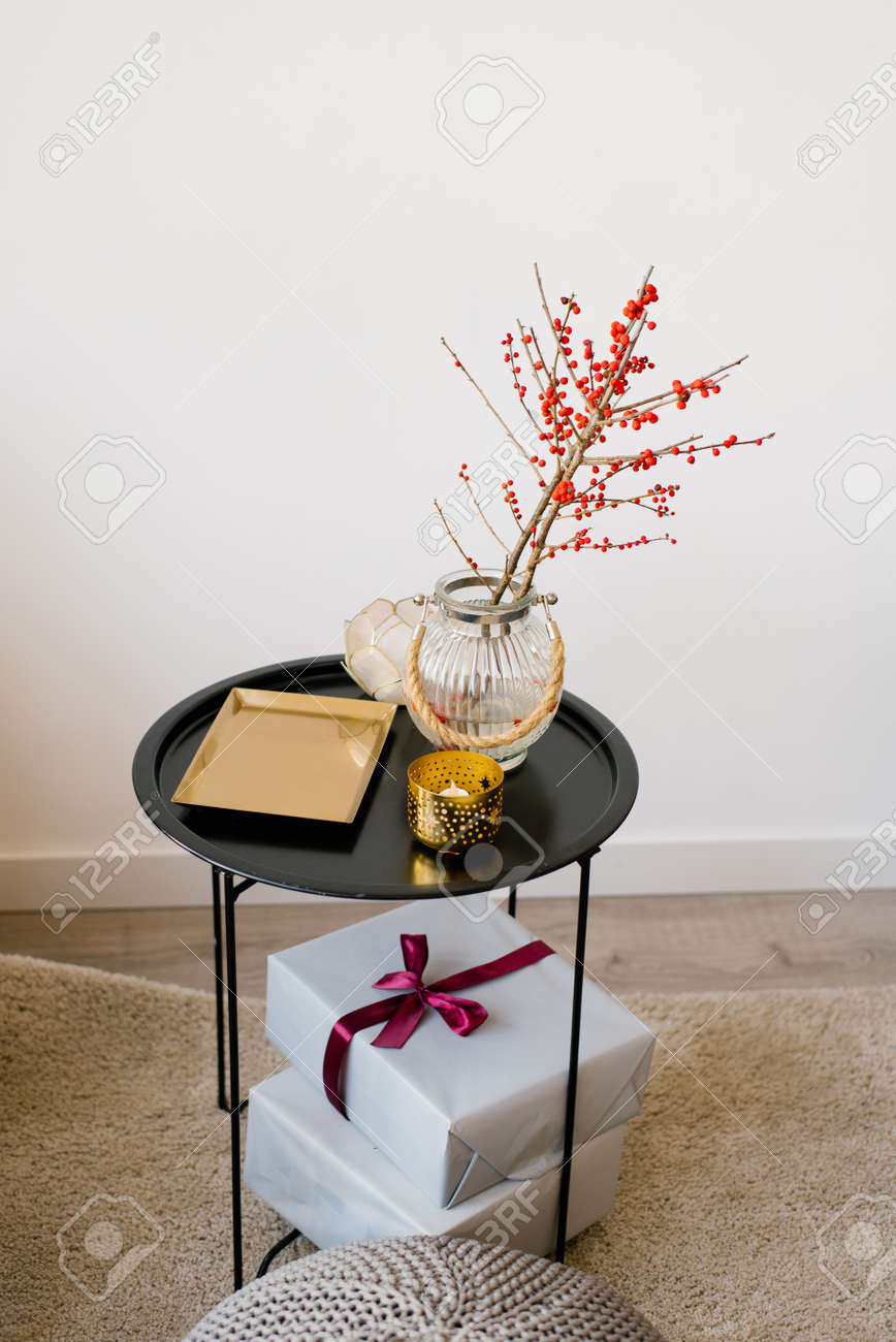 A coffee table with a gold tray, branches with red berries in a glass vase and gift boxes with ribbons and a bow on it - 134018868