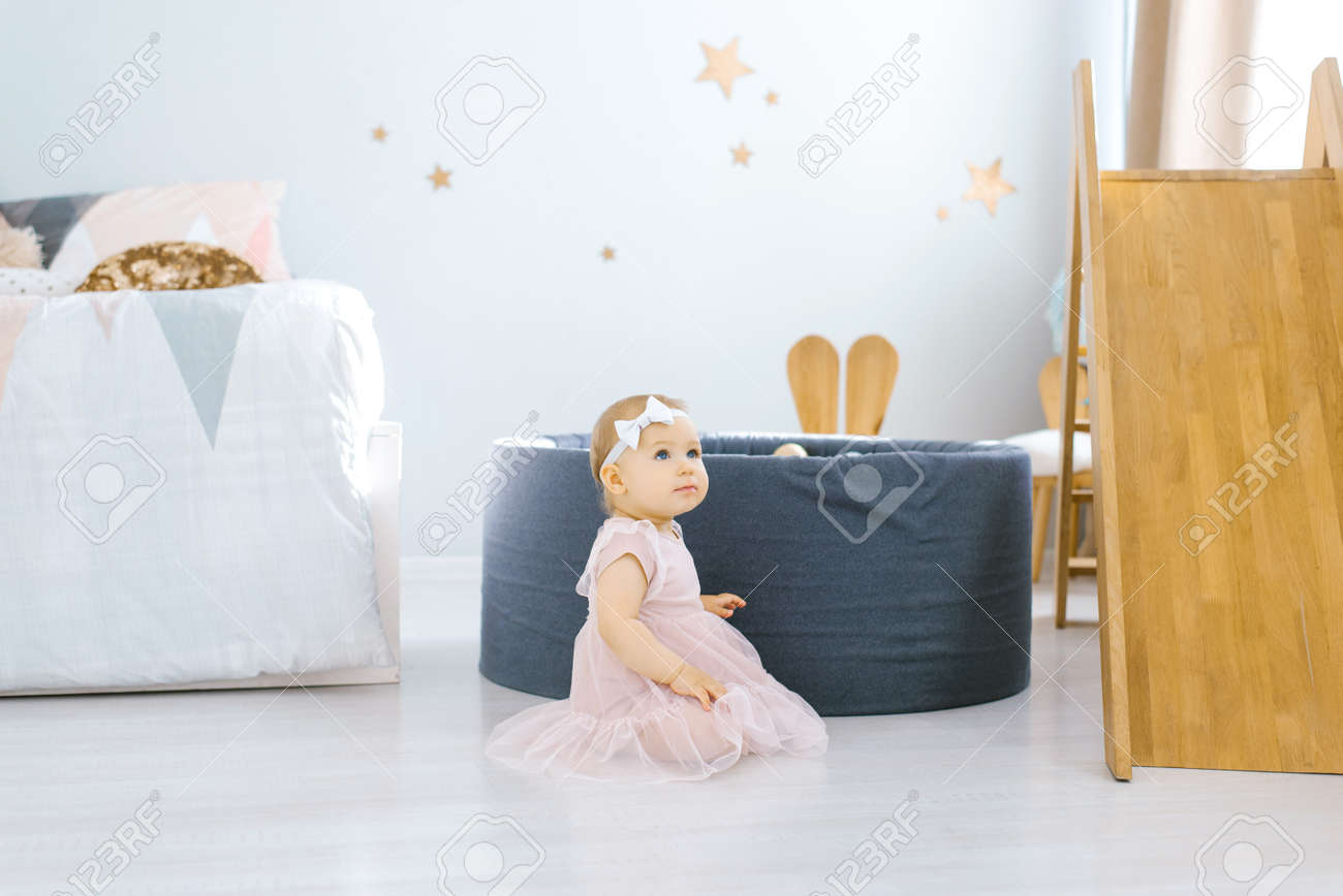 Little girl 1 year old sits on the floor in the children's room - 168588099
