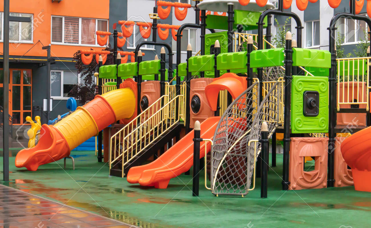 A courtyard of high-rise buildings with a new modern colorful and large playground on a rainy summer day without people. Empty outdoor playground. A place for children's games and sports - 173010686