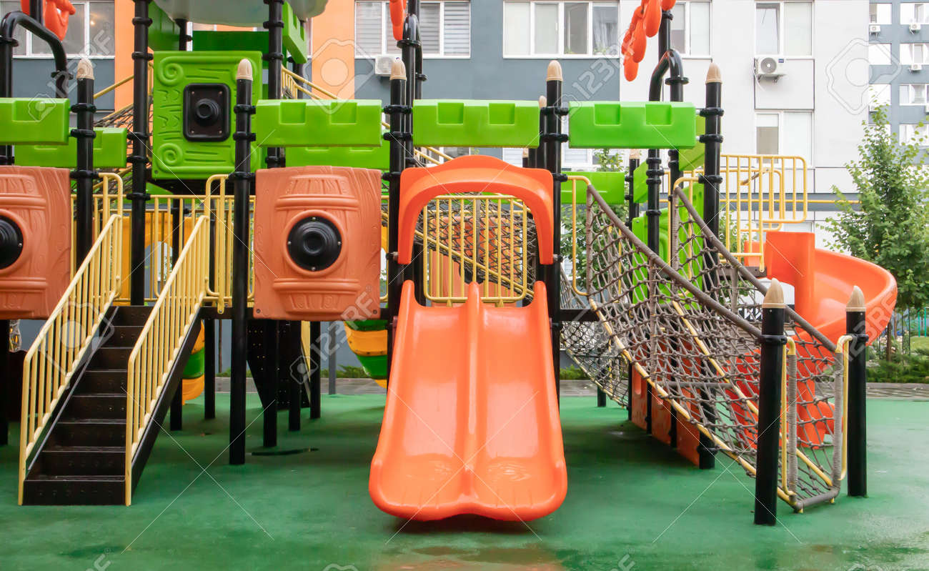 A courtyard of high-rise buildings with a new modern colorful and large playground on a rainy summer day without people. Empty outdoor playground. A place for children's games and sports - 173010693