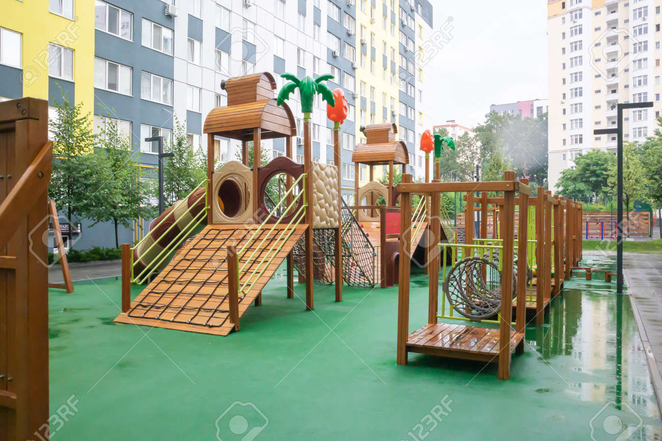 A courtyard of high-rise buildings with a modern and large playground made of wood and plastic on a rainy summer day without people. Empty outdoor playground. A place for children's games and sports - 173010742
