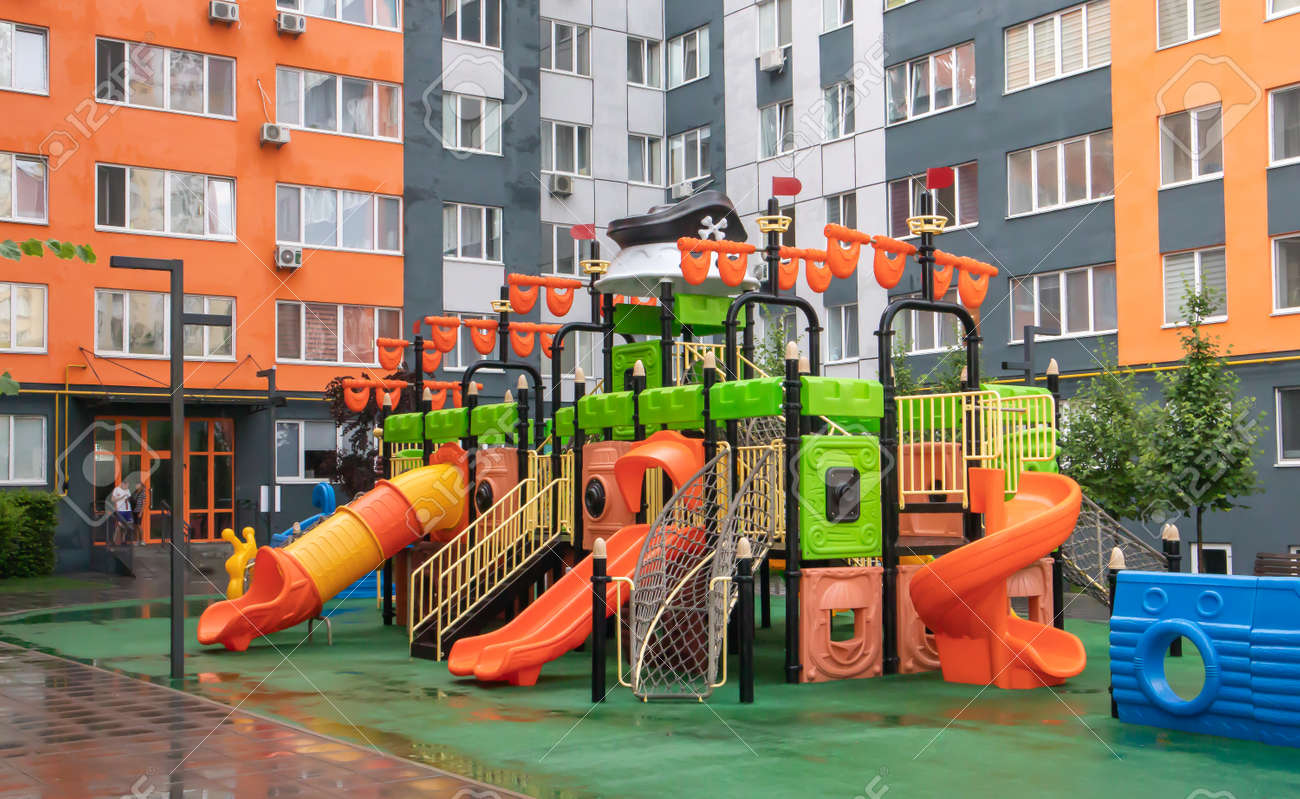 A courtyard of high-rise buildings with a new modern colorful and large playground on a rainy summer day without people. Empty outdoor playground. A place for children's games and sports - 173011333