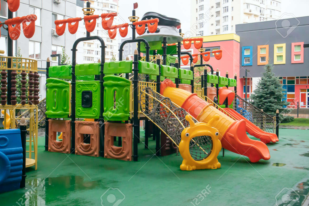 A courtyard of high-rise buildings with a new modern colorful and large playground on a rainy summer day without people. Empty outdoor playground. A place for children's games and sports - 173011337