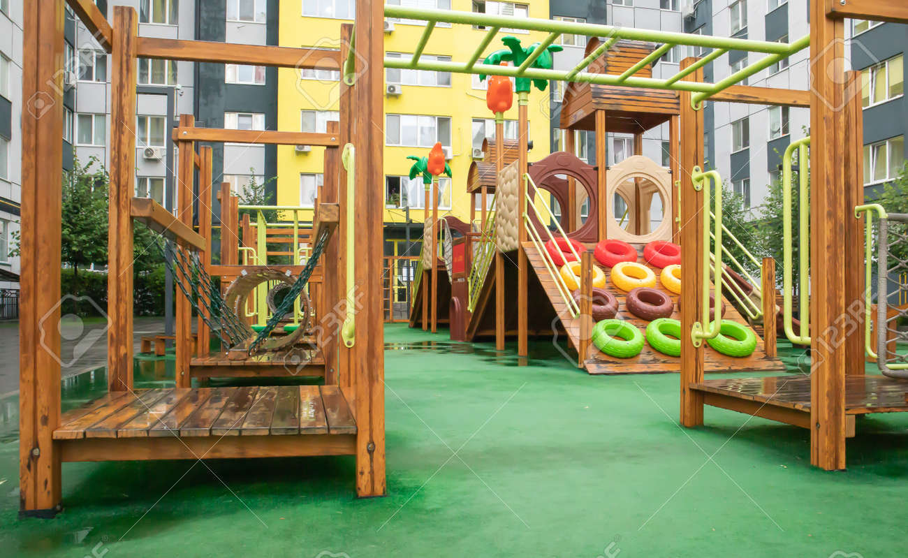 A courtyard of high-rise buildings with a modern and large playground made of wood and plastic on a rainy summer day without people. Empty outdoor playground. A place for children's games and sports - 173011340