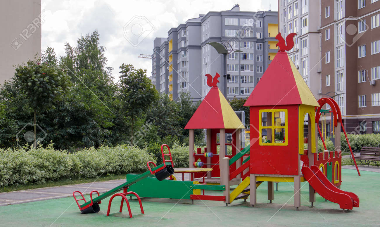 An empty modern playground in the courtyard of residential buildings without people and children. Security and protection measures against COVID-19 in the city park. The concept of childhood is over - 173011433