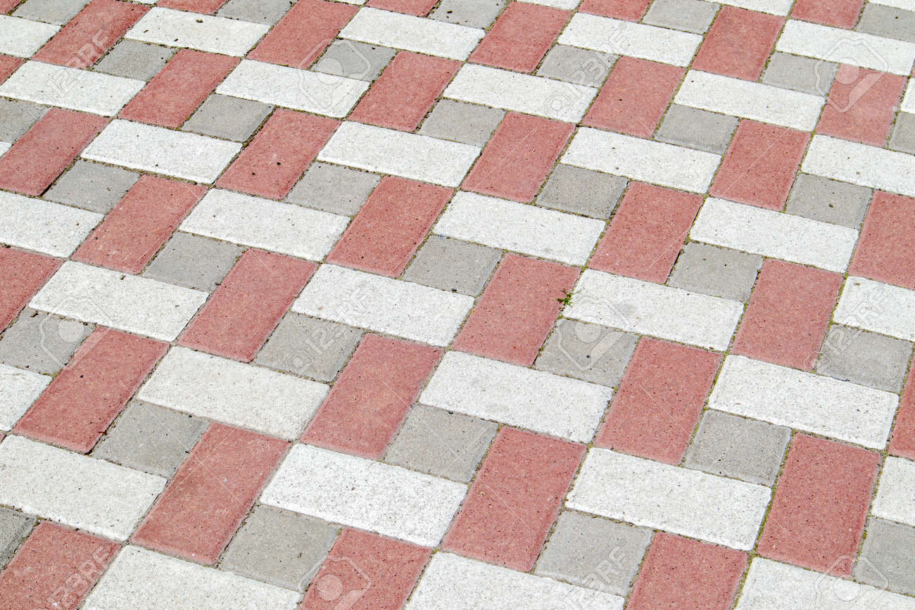 Concrete or paved newly laid gray and red paving slabs or stones for floors or walkways. Concrete paving slabs in the backyard or road paving. Garden brick path in the courtyard on a sandy foundation - 173265712