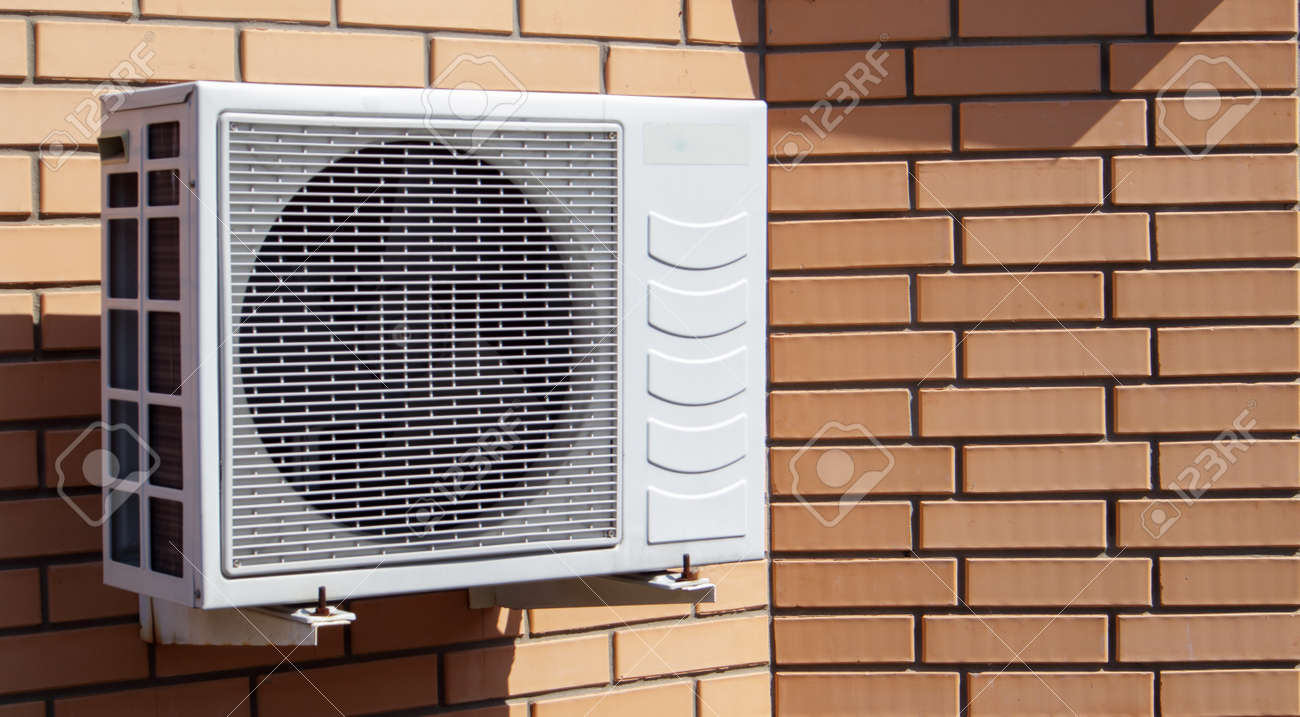 Close-up shot of a modern climate control unit against the background of a brick wall of the facade of a house outside. Air conditioner on the wall with space for text. Air compressor - 173122850
