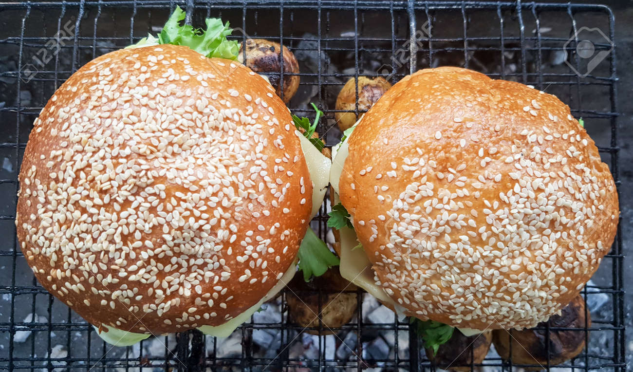 Close-up of two large DIY hamburgers in the park on a barbecue, rest and cooking on a picnic in the summer, food, delicious, bright colors. Unhealthy food concept. Fast food. Flat lay - 173026354