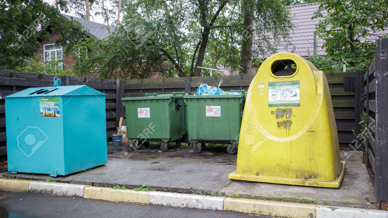 Four plastic and metal garbage bins for sorting waste in the courtyard of a residential street. Garbage cans in the courtyard of a residential building. Ukraine, Kiev - August 29, 2021 - 173496347