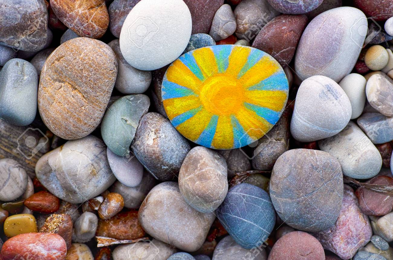 Bright sun painted on pebble. Pebbles background. - 90180565