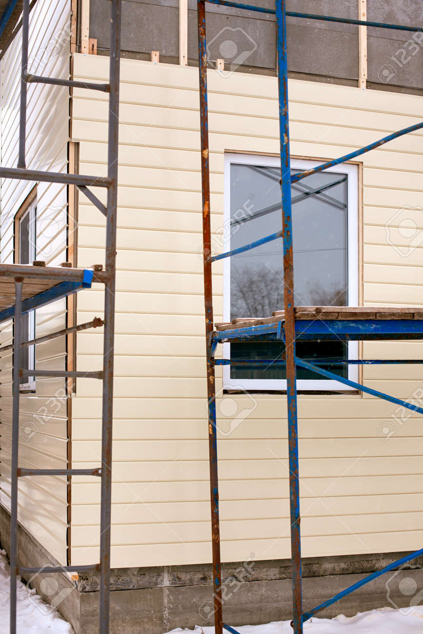 Beige siding covering the wall and scaffolding around house