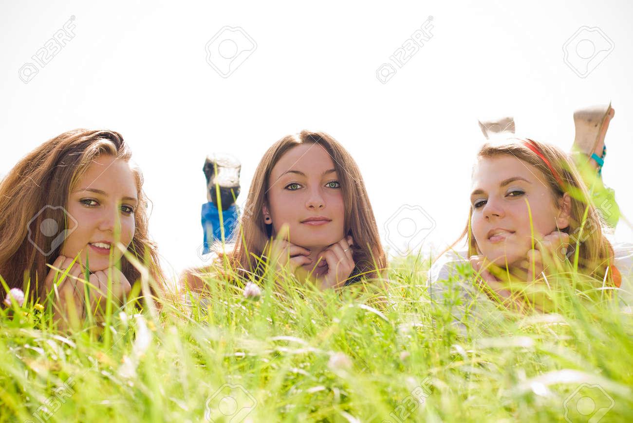 Three teen friends lying in green grass Stock Photo - 17198073