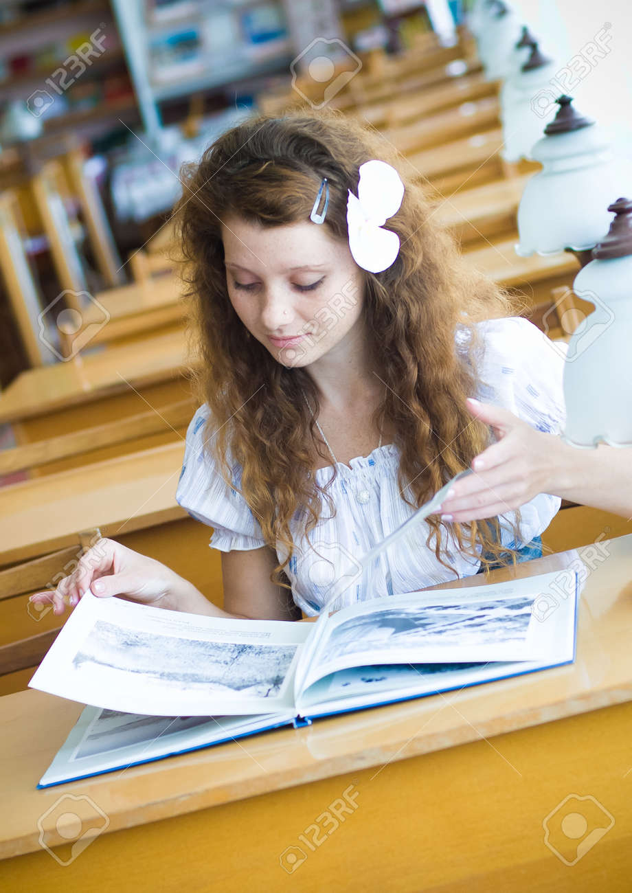 Young pretty female student in library Stock Photo - 17198579