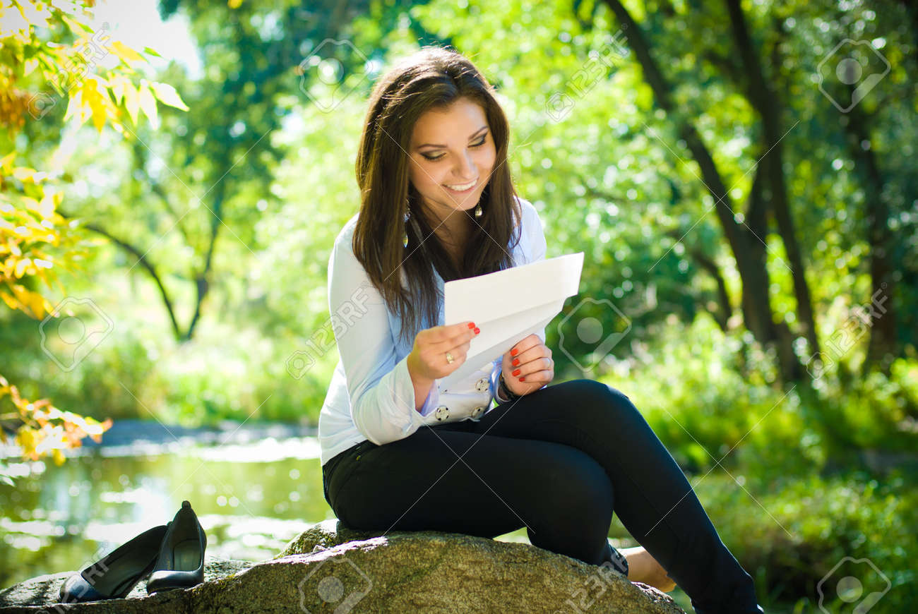Young beautiful woman reading good news in park Stock Photo - 14335046