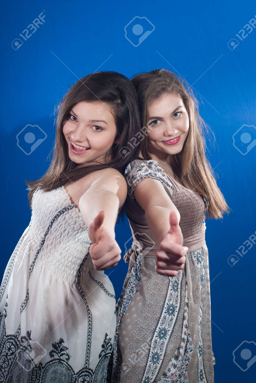 Two happy teenage friends showing thumbs up on blue screen background Stock Photo - 17492706