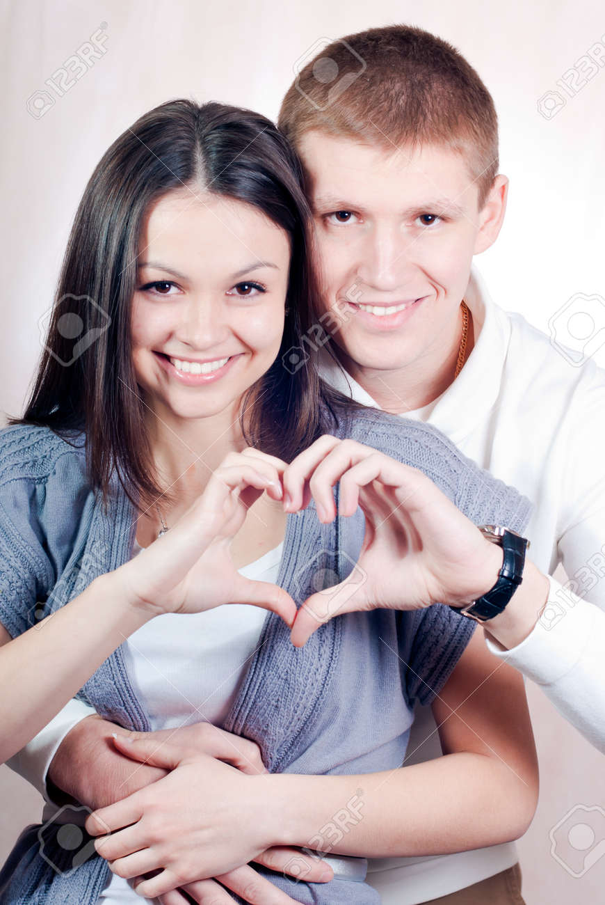 Happy young couple with heart symbol embracing and smiling studio portrait Stock Photo - 17631089