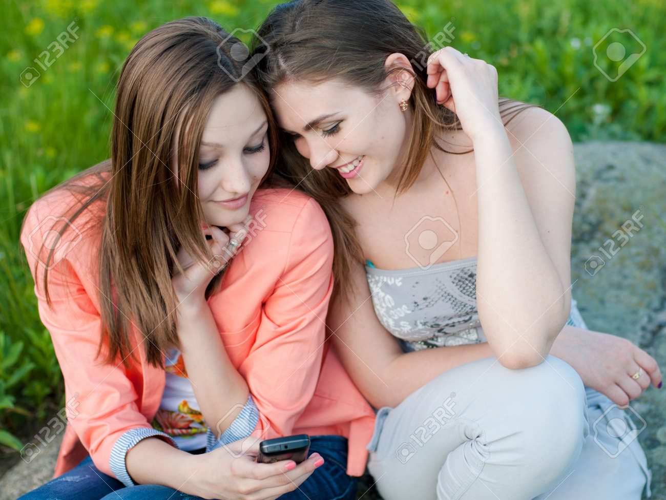 Two happy teenage girl friends reading message on mobile Stock Photo - 17602253