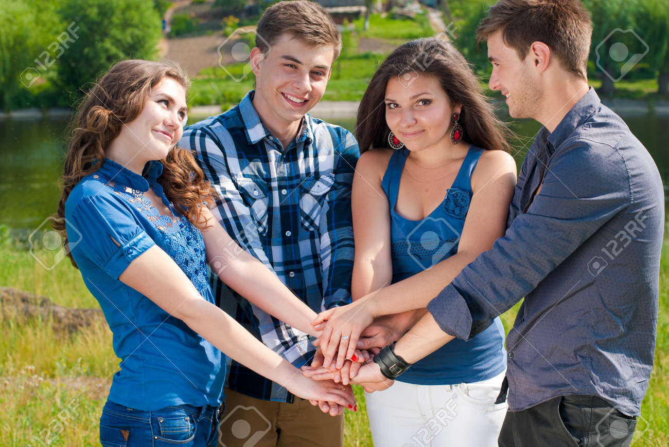 Happy four teenagers shaking hands