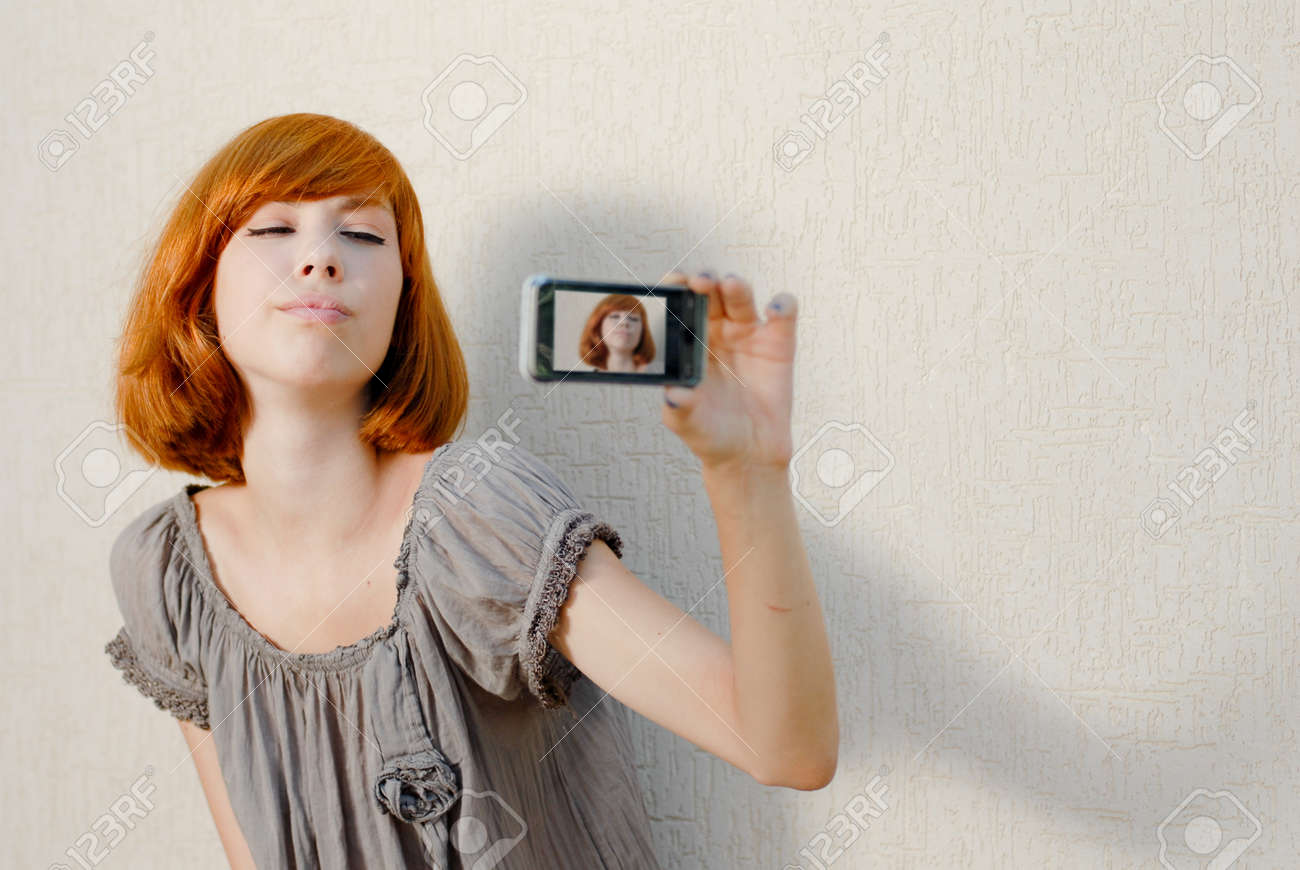 Young beautiful woman taking picture of herself on mobile touch phone - 18008738