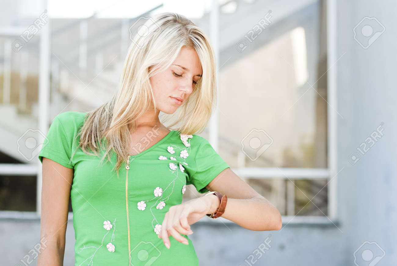Young woman looking on hand watch - 18184592