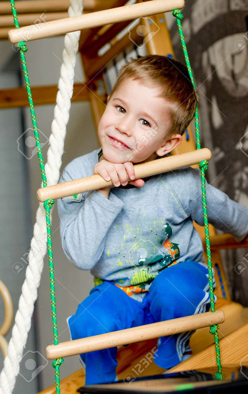 The boy of preschool age makes exercises on a gym wall bars Stock Photo - 18521266