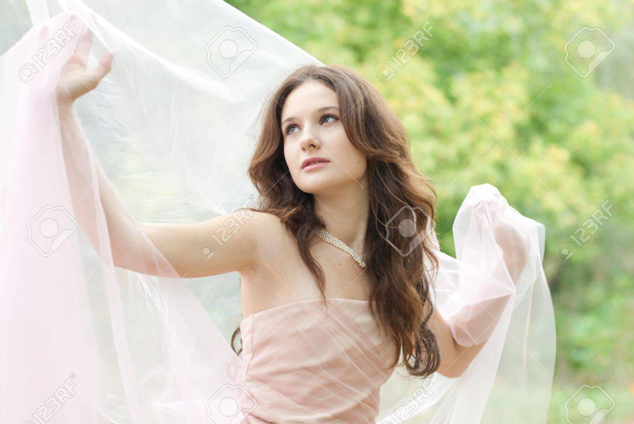 Beautiful young sensual woman with white color silk scarf and long wavy hair holding herself Stock Photo - 18539374