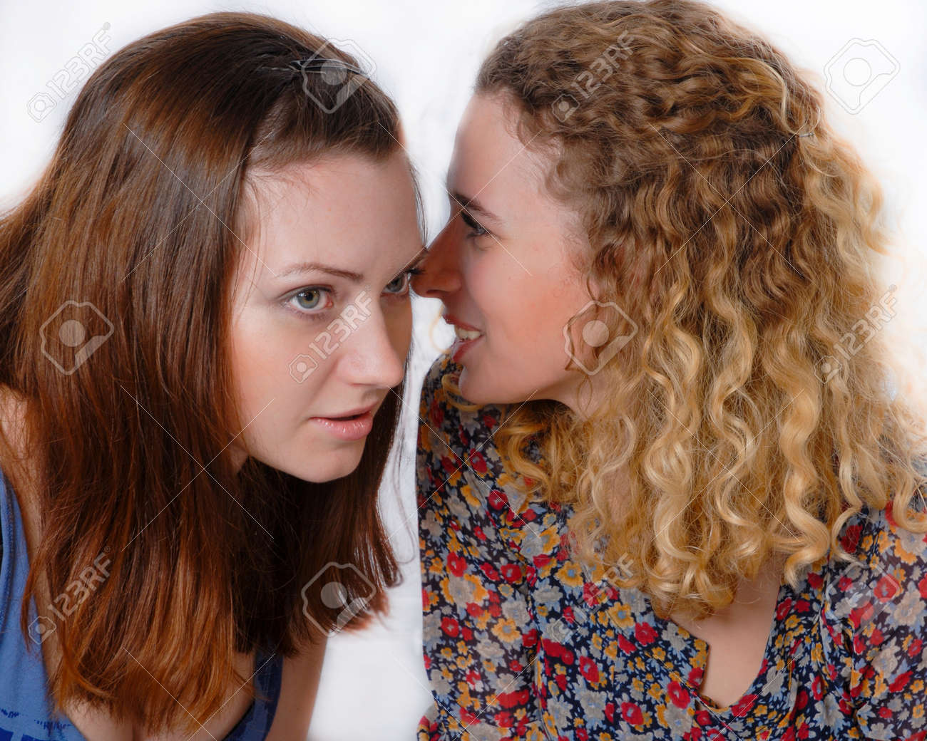 Two beautiful young girls talking privately on white background Stock Photo - 20108640