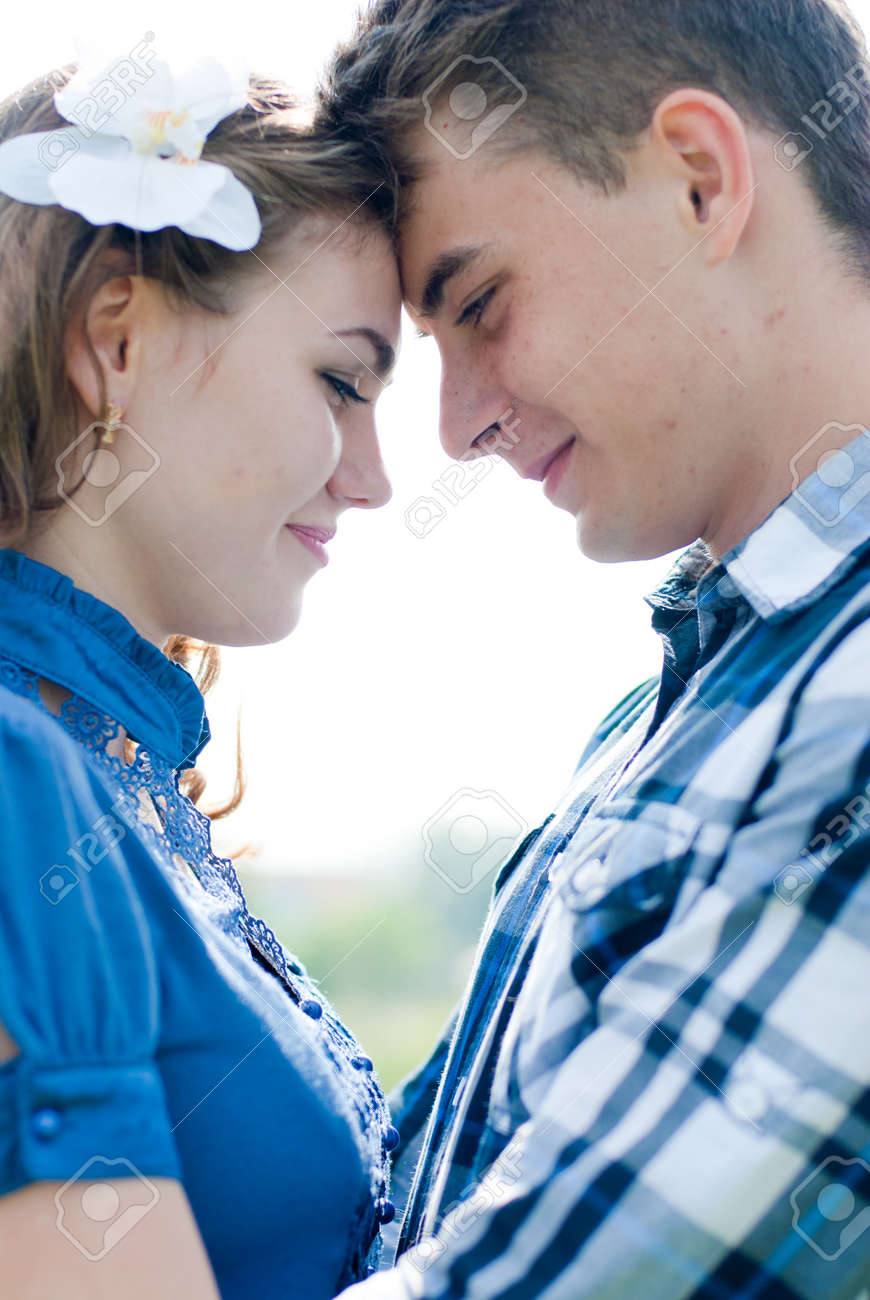 Happy teenage couple boy and girl embracing over blue sky background Stock Photo - 20108353