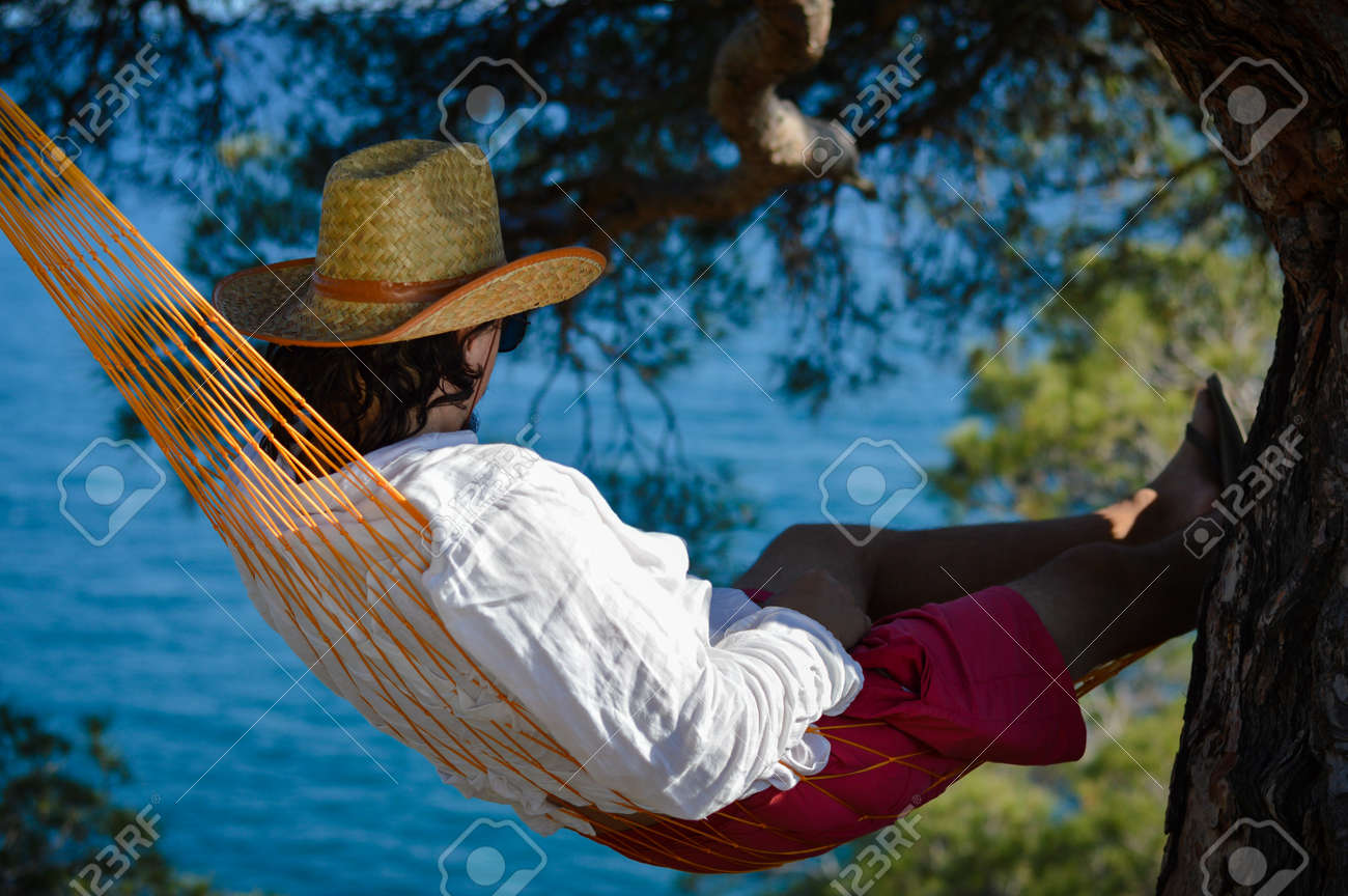 Lazy time Man in hat in a hammock on a summer day - 20897732