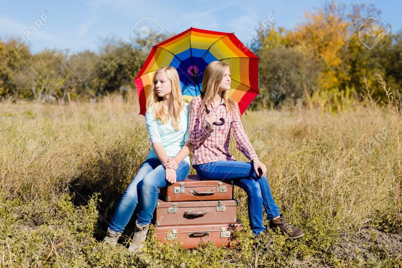 banque dimages drle heureux adolescentes assis sur des valises rtro et un parapluie color sur le champ de fond - Parapluie Color