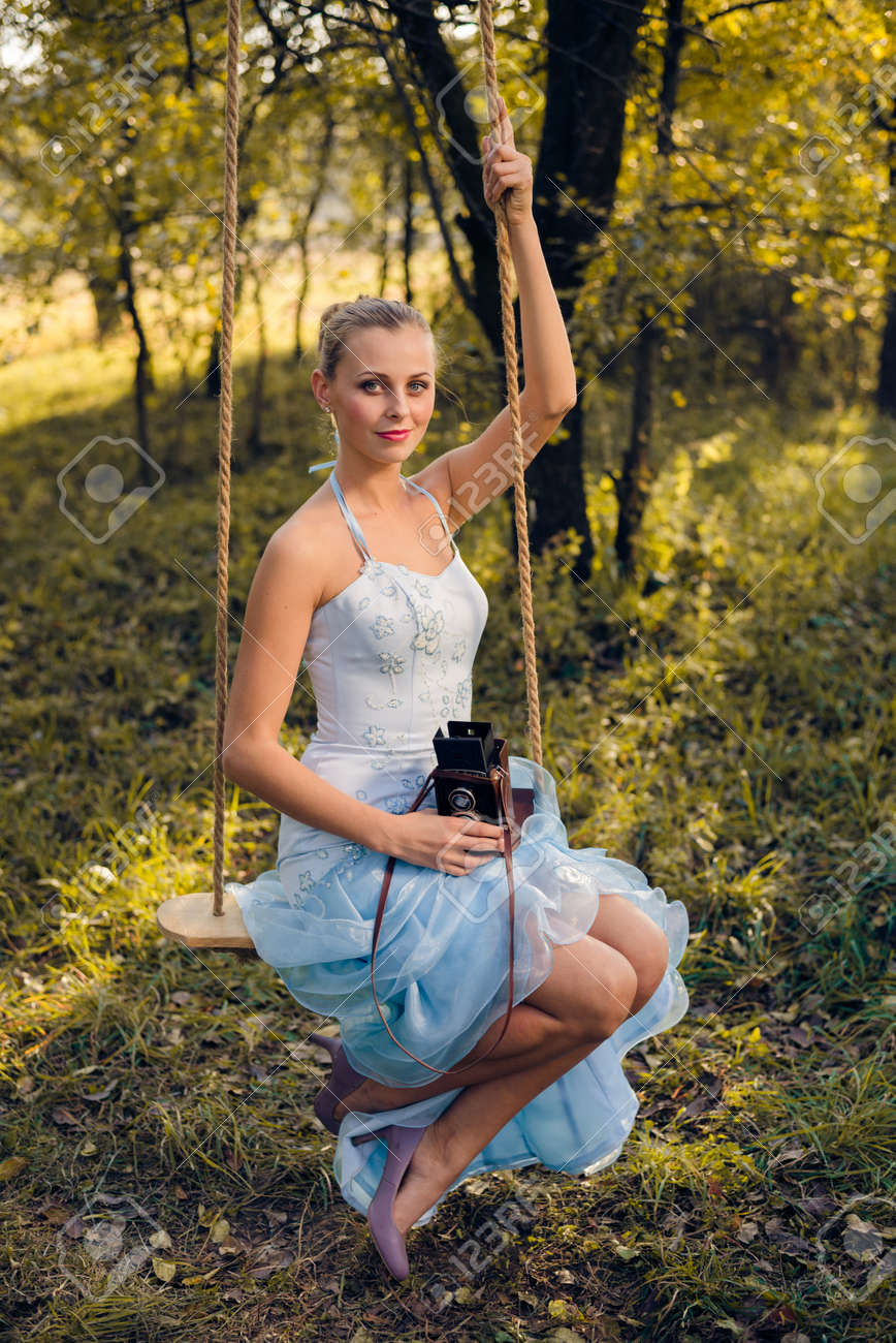 Beautiful Young Woman In Prom Dress Sitting On Swing With Retro ...