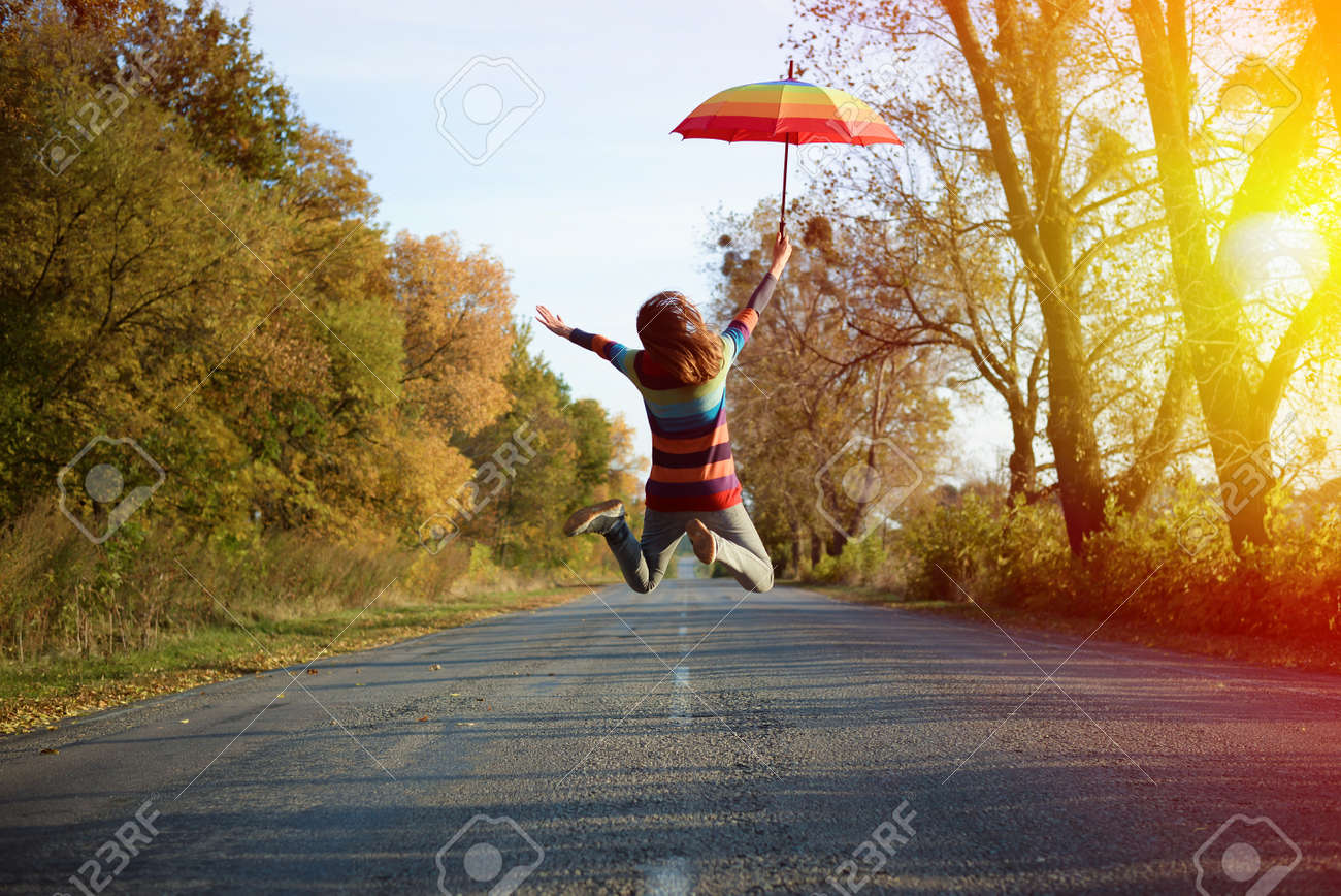 Conceptual picture of jumping lady holding umbrella with arms sideways on empty country road in autumn - 45045487