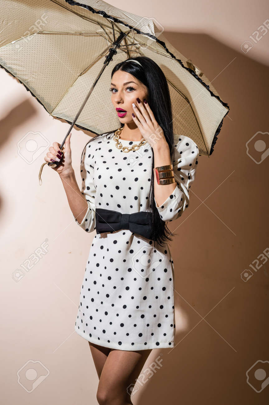 71eb99b5a Stock Photo - Young happy pinup woman with umbrella wearing polka dot dress  over white background