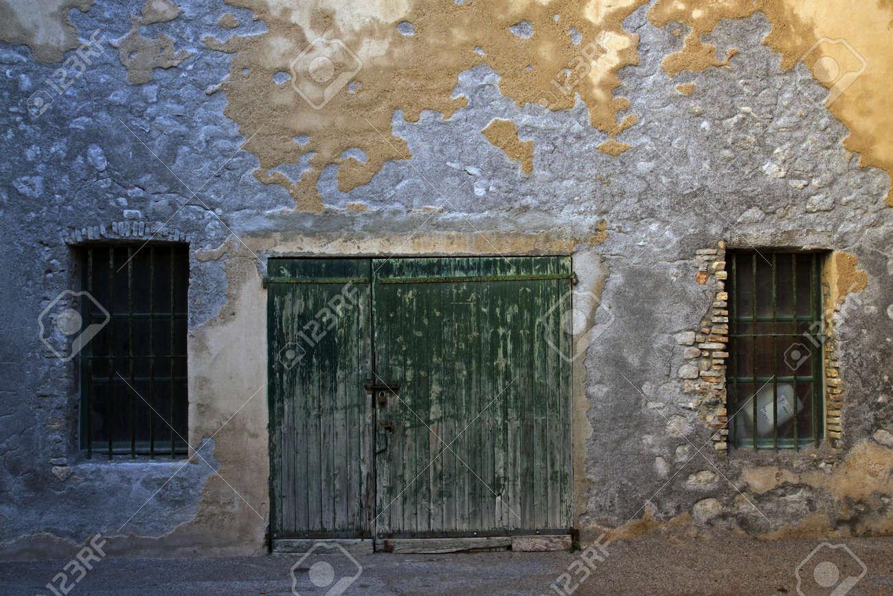 Vieilles Portes En Bois Et Deux Fenêtres Grillagées. Mur Patiné De ...