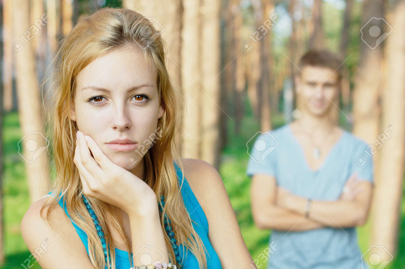 Upset girl with her boyfriend at the background Stock Photo - 10335648