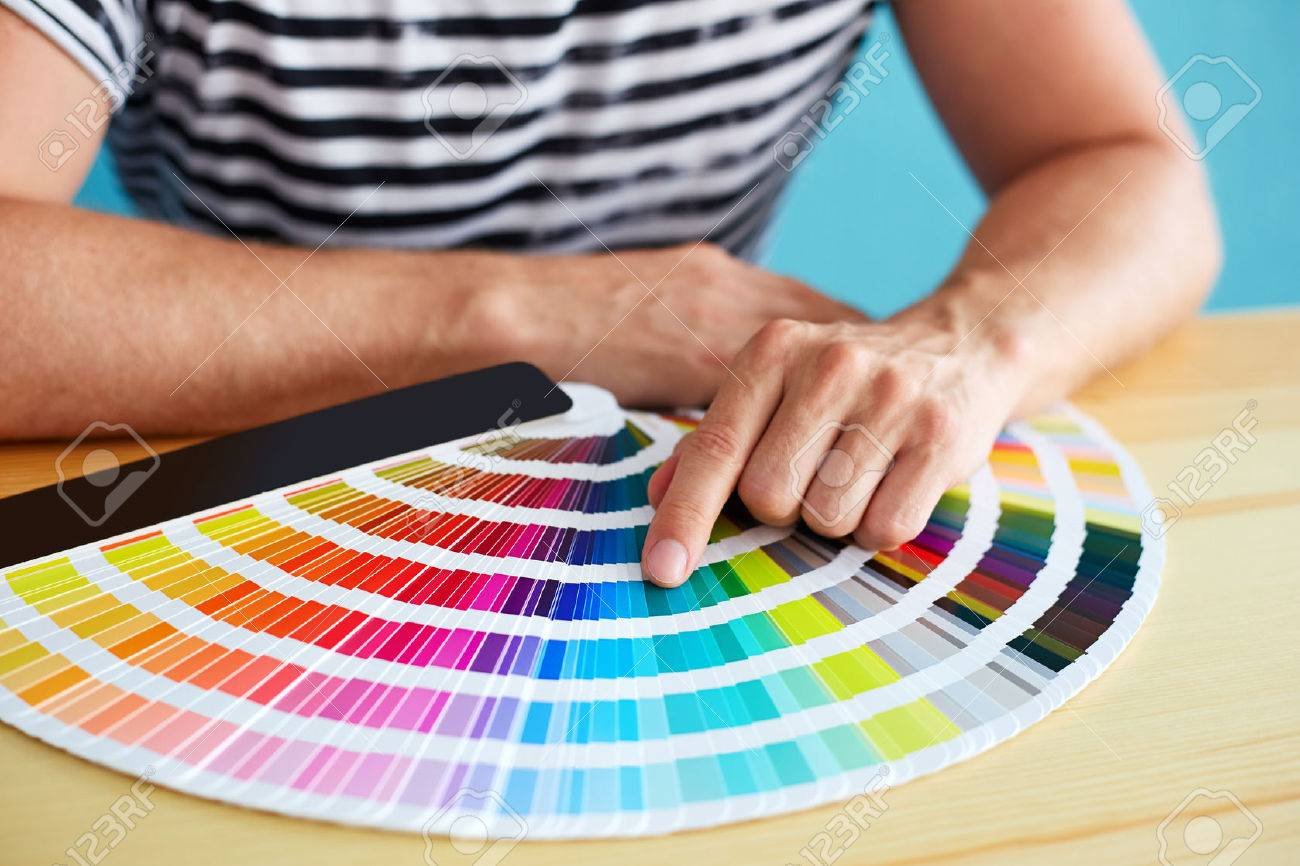 Graphic designer choosing a color from the sampler - 43778616