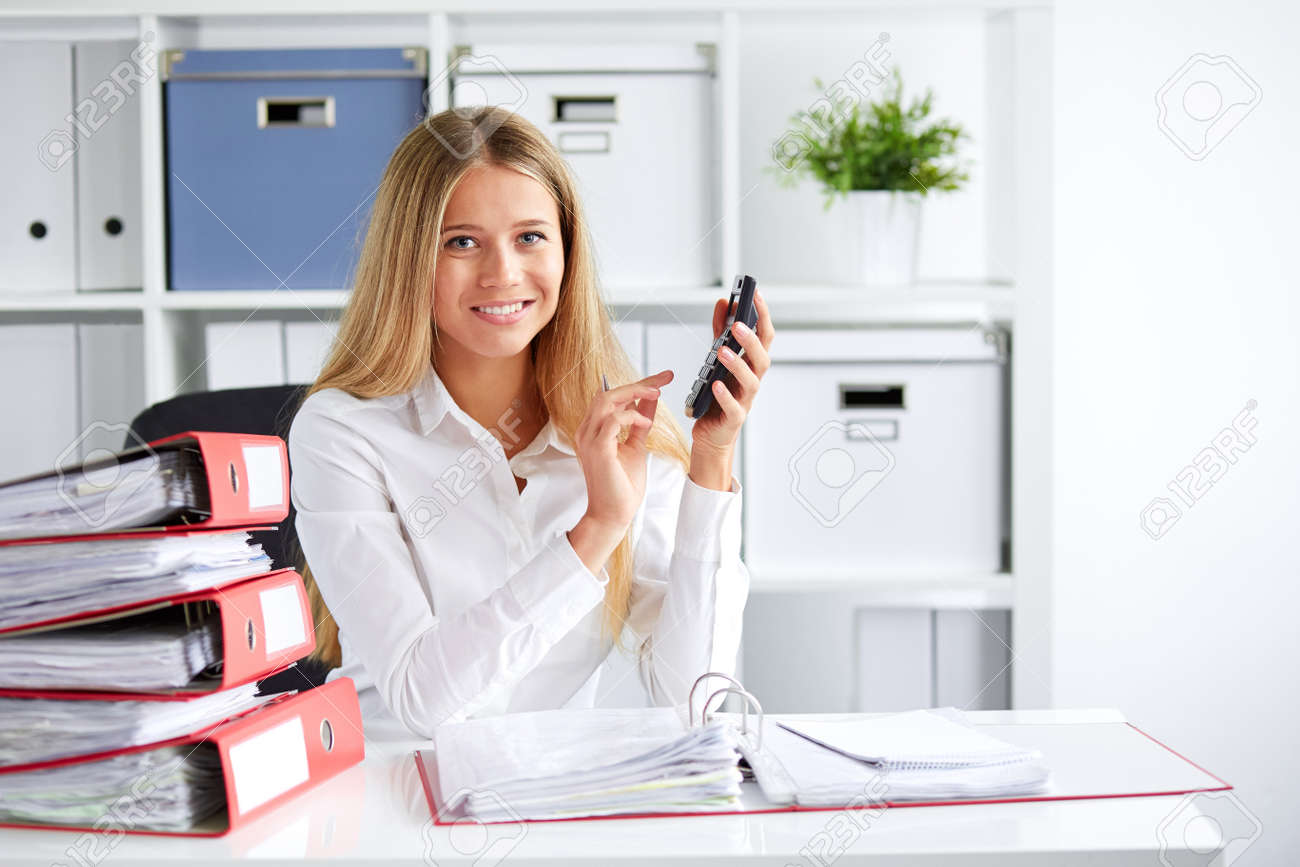 Smiling business woman calculates tax at desk in office - 51471613